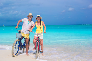Young happy couple with bikes on white tropical vacation