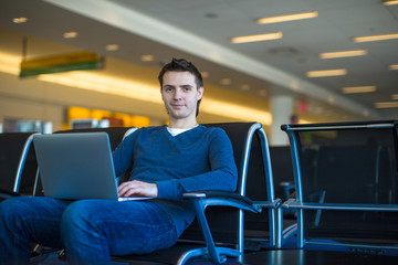 Young man with a laptop at the airport while waiting his flight