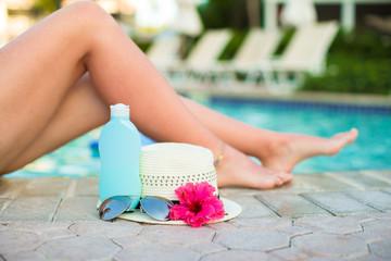 Suncream, hat, sunglasses, flower and tanned female legs near