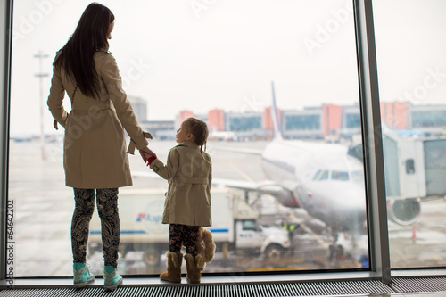Mother and little daughter looking out the window at airport - 64642202