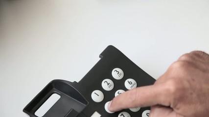 Dedos pulsando números de teléfono fijo