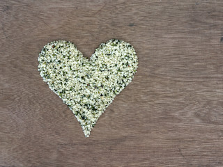 Shelled hemp seeds shaped in a heart symbol