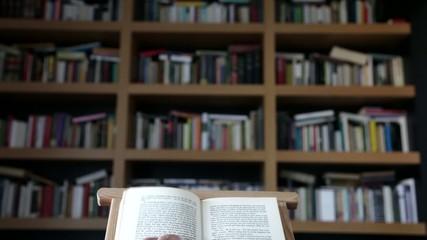 Mano pasando página de libro con librería al fondo