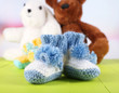 Crocheted booties for baby and toys,on color background