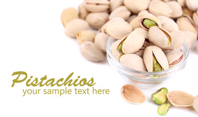 Pistachio nuts in glass bowl isolated on white