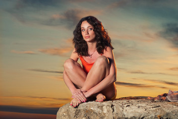 young woman sitting on the edge of rock at sunset sky