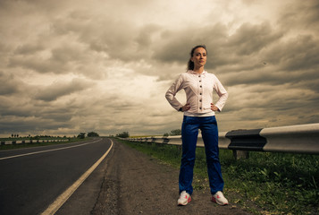 young pretty strong woman at stormy roadside