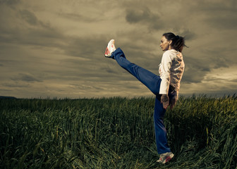 young strong woman making exercise at spring wheat field