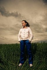 young sportive woman standing at spring wheat