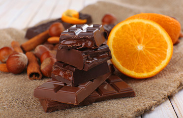Chocolate, orange and nuts on table