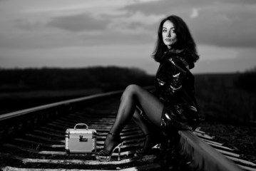 young woman in black pantyhose sitting at rail tracks