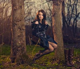 sexy brunet on a wooden swing