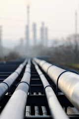 crude oil pipeline and oil  refinery against light