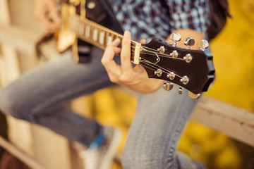 man in jeans playing guitar outdoor