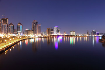 Skyline of Sharjah City at dusk, United Arab Emirates