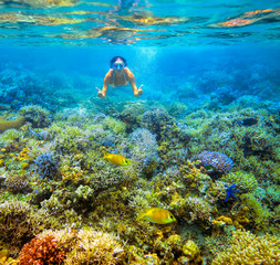 Woman snorkeling in beautiful coral reef with lots of fish.