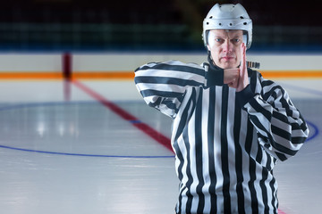 Hockey referee demonstrate a penalty