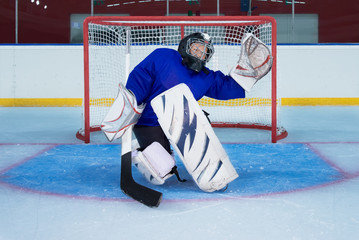 Young hockey goalie catching a flying puck
