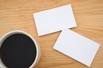 blank business cards and coffee on wooden table