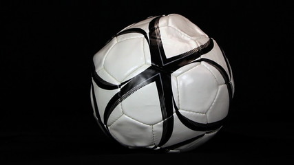 Soccer ball is inflating on a black background, close up