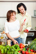 Happy man and woman with vegetables in kitchen