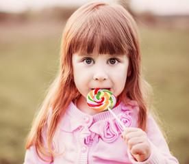 little girl  holding lollipop in her hand