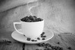 Vintage cup of roasted coffee beans in black and white tone