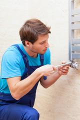 Young repairman fixing heater