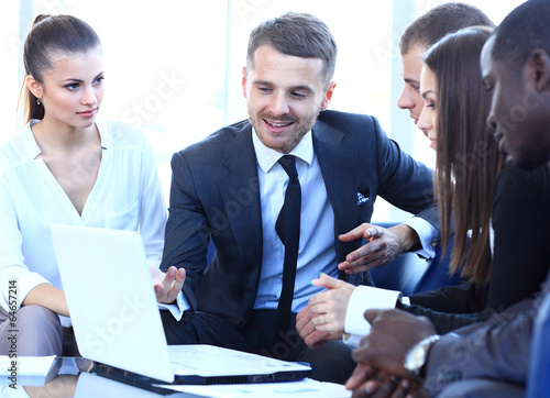 Group of friendly businesspeople gathered in front of laptop