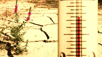 Arid cracked ground and overheated thermometer