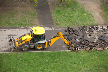 Heavy road construction machine breaks up old asphalt