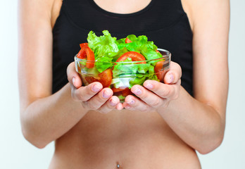 part of a female slim sporty body. vegetables salad.