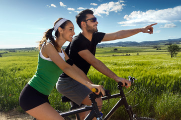 Happy young  couple on a bike ride in the countryside