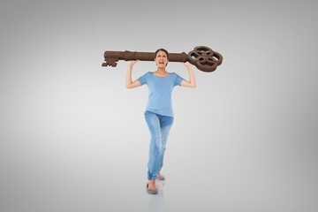 Composite image of annoyed brunette carrying large key