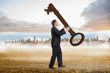 Composite image of stressed businessman carrying large key
