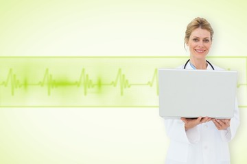 Composite image of blonde doctor using laptop