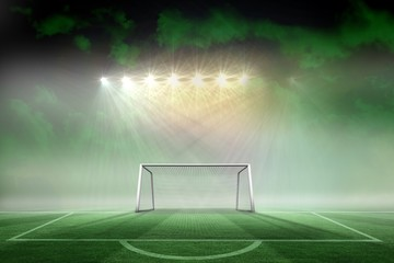 Football pitch and goal under spotlights