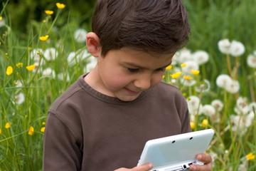 Junge beim Nintendo spielen im Garten 3