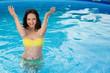 Bathing beautiful woman posing in her bikini in the pool
