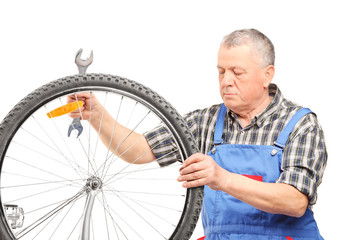 Mature bicycle mechanic looking at a wheel