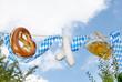 Bier, Breze und Weisswürste vor weiss-blauem Himmel