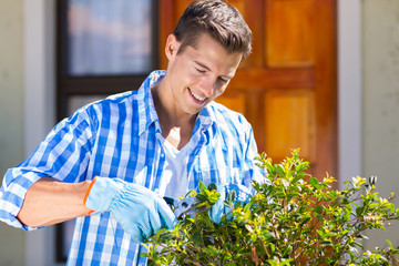 man pruning a shrub by house front door