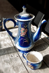 Blue and white teakettle with pink flower and blue & white cup.