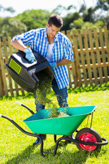 young man emptying lawnmower grass into a wheelbarrow