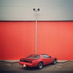 red car in front of red wall in Berlin
