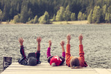 color image of three children siting on pontoon on lake