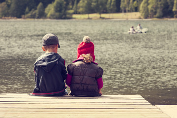 color image of two children siting on pontoon on lake