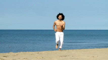 Handsome man jogging on beach taking stress out