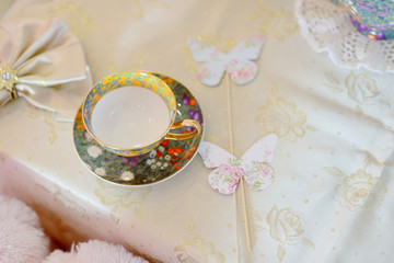 on a table with a white tablecloth color tea cup and a napkin an
