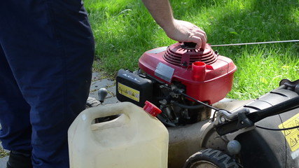 gardener hand open and fill empty lawn cutter mower fuel tank